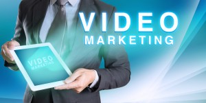 businessman holding tablet with VIDEO MARKETING word with abstract background for Business
