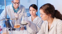 Women Science Students Studying Chemistry with Professor in Laboratory Horizontal